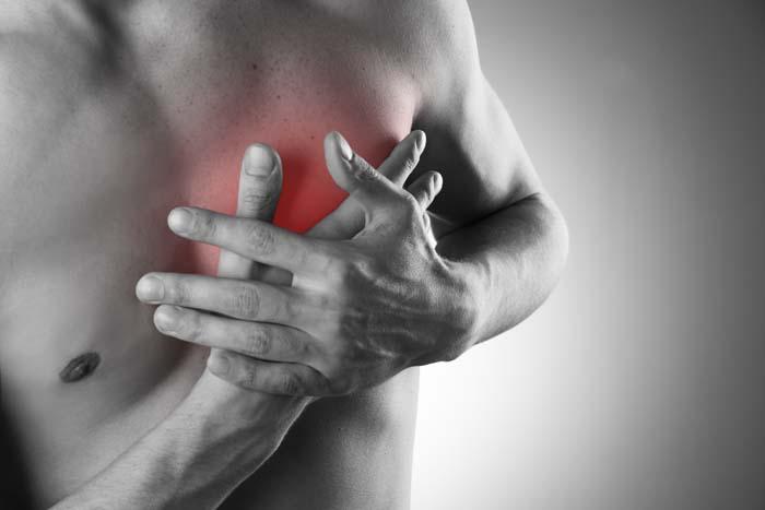 mann mit nacktem oberkoerper haelt sich beide haende an die brust weil er schmerzen durch einen herzinfarkt hat