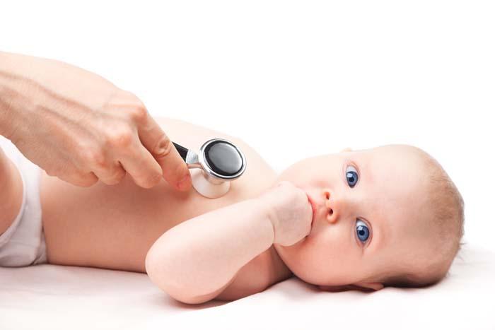 nahaufnahme eines babys bzw kindes. es wird von einem kardiologen mit dem stethoskop am herzen untersucht